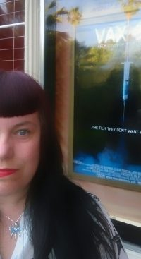 photo of Dawn in front of Vaxxed movie poster outside theater